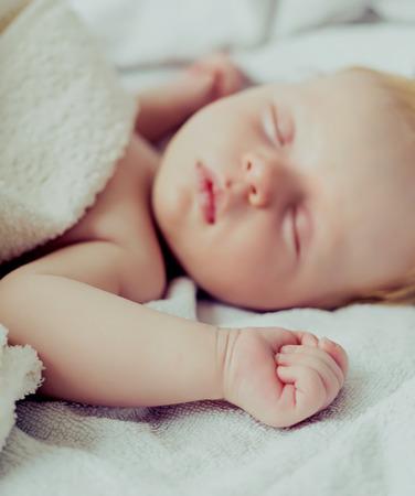puños cerrados: bebé durmiendo dos meses de vida, se centran en la mano izquierda Foto de archivo