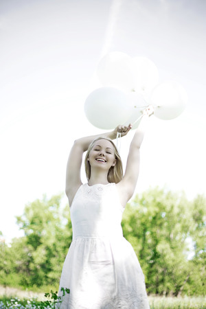 underarms: happy young woman with white balloons in the summer park Stock Photo