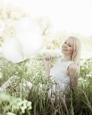 outsides: happy young woman with white balloons in the summer park Stock Photo