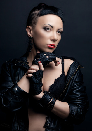 woman with modern unusual haircut with shaved sides and a fringe, wearing leather, against dark studio background photo