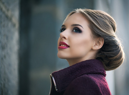 beautiful woman with bright makeup wearing a warm jacket in the street