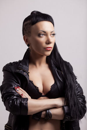 woman with modern unusual haircut with shaved sides and a fringe, wearing leather, against grey studio background photo