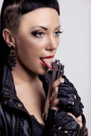 police girl: woman with modern unusual haircut with shaved sides and a fringe, holding a gun, against grey studio background