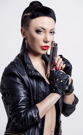 woman with modern unusual haircut with shaved sides and a fringe, holding a gun, against grey studio background