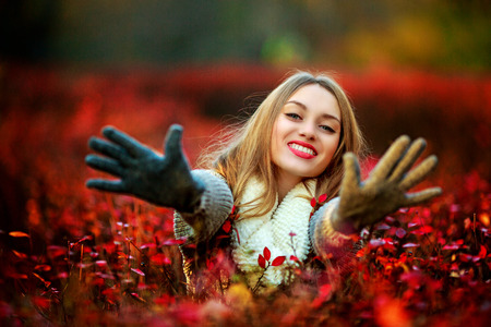 passtime: happy young woman in the autumn park, stretching hands to us Stock Photo