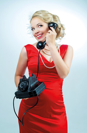 beautiful young blond retro woman with a telephone, retro style photo