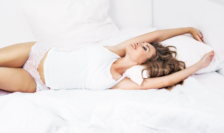 young woman with long beautiful hair waking up and stretching in bed at home photo