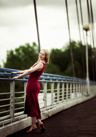 outsides: beautiful happy blond woman on the bridge on a summer day