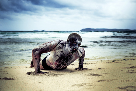 malevolent: young man with a zombie body painting, covered with blood on the beach  (halloween topic)