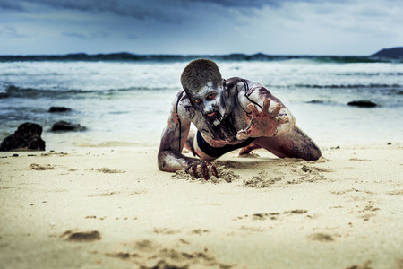 ghoulish: young man with a zombie body painting, covered with blood on the beach  (halloween topic)