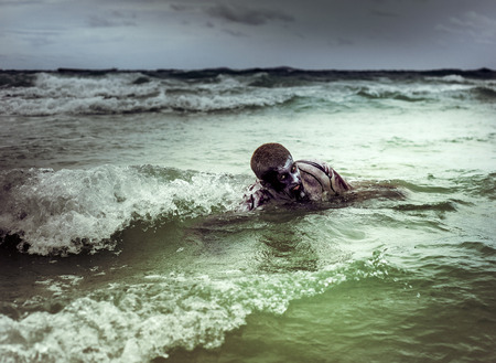 young man with a zombie body painting, covered with blood swimming in the ocean  (halloween topic) photo