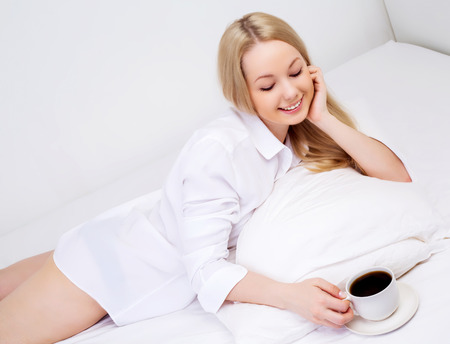 woman drinking tea: beautiful woman with a cup of coffee in bed at home Stock Photo