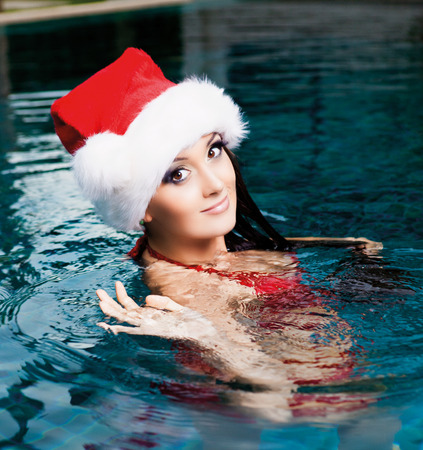 beautiful young woman wearing  Santas hat in the swimming pool (Christmas topic) photo