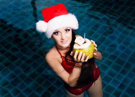 swimming costumes: beautiful young woman wearing  Santas hat and drinking coconut milk in the swimming pool (Christmas topic) Stock Photo