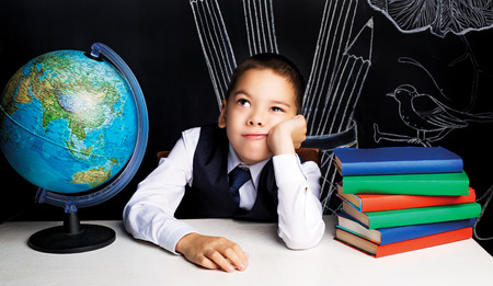 seven year old school boy sitting by the table and feeling bored photo