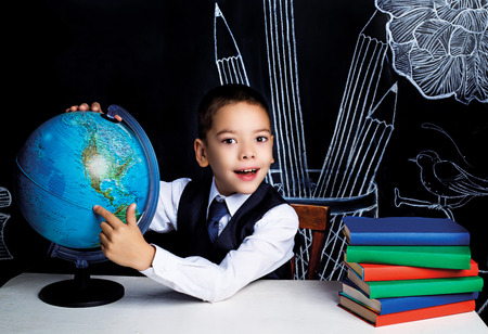 seven year old: seven year old school boy sitting by the table with a globe