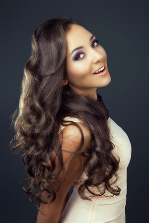 beautiful young brunette woman with long curly hair, against dark grey studio background Stock Photo
