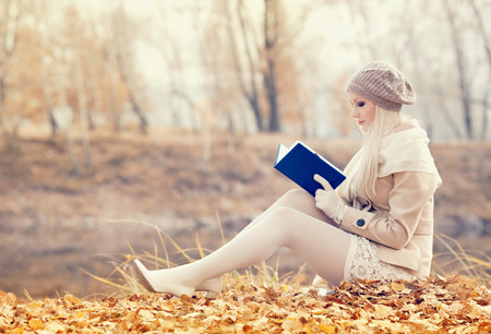 the girl in stockings: beautiful woman reading a book in the park