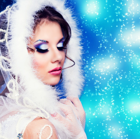 sexy glamour: model with bright party makeup agaist blue background, winter topic