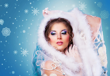 female christmas: model with bright party makeup agaist blue background, winter topic