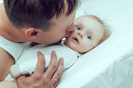 two months: father kissing his two months old baby, in bed at home Stock Photo