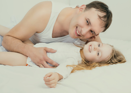five years old: father and his five years old daughter, in bed at home