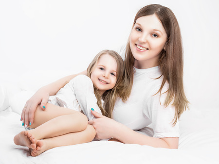 five years old: giovane bella madre e sua figlia di cinque anni, a letto a casa Archivio Fotografico