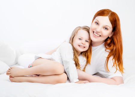 five years old: young beautiful mother  and her five years old daughter, in bed at home Archivio Fotografico