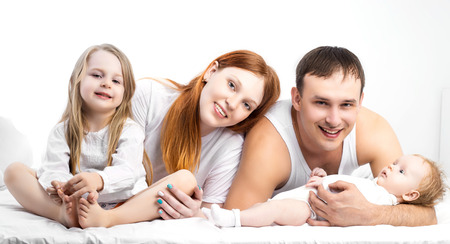 five years old: happy family: mother, father, their five years old daughter and their two months old baby in bed at home