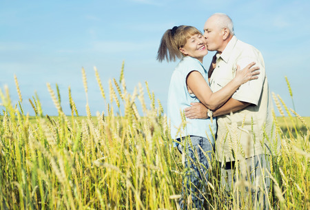 affectionate: happy couple: 68 year old man and 65 year old woman outdoor at the wheat field