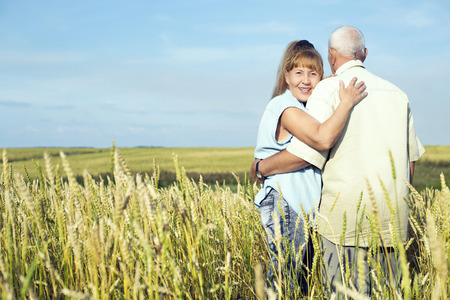 woman in field: happy smiling couple: 68 year old man and 65 year old woman outdoor at the wheat field