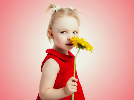 five year old: five year old gorl with a yellow flower, isolated against studio background Stock Photo