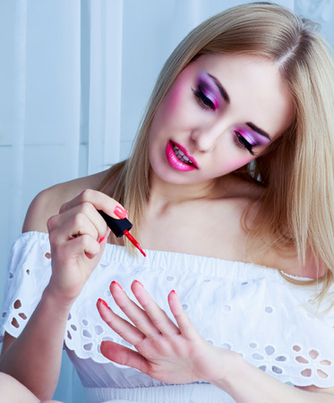 barbie: pretty woman with bright pink makeup applying nail polish