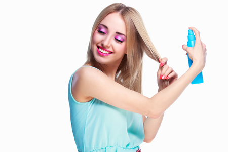 blue dress: pretty happy woman with a hair spray isolated against white studio background