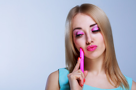 barbie: thoughtful woman with a pen, against blue background