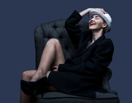 classy: happy laughing woman wearing a suit and a hat, against red studio background