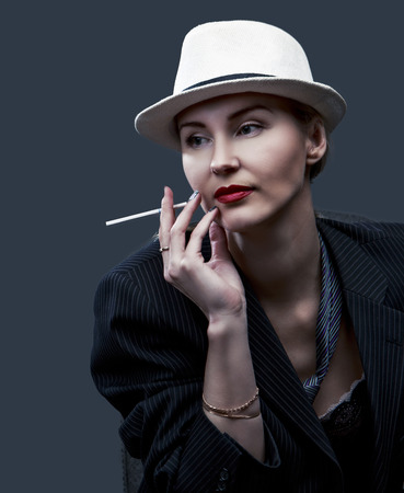 an adult person: sexy woman wearing a suit and a hat, against red studio background