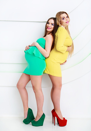 pregnant blonde: two happy laughing pregnant women, studio shot