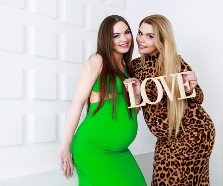 girl portrait: two happy pregnant women, studio shot