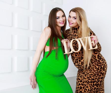 studio portrait: two happy pregnant women, studio shot
