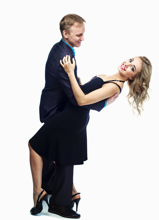 sexy young woman: happy young couple dancing, isolated against white studio background