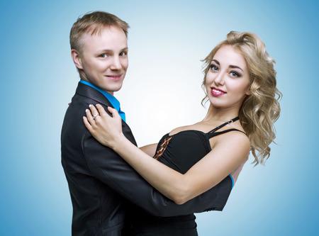 make love: feliz joven pareja de baile, aislado contra el fondo azul del estudio
