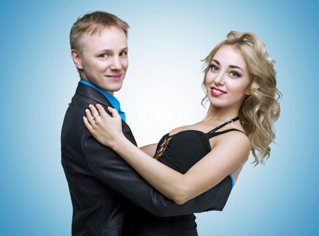 faire l amour: happy young couple dancing, isolated against blue studio background Banque d'images