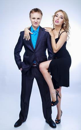 faire l amour: confiant jeune homme et une belle femme blonde, le s�duire, contre fond bleu studio