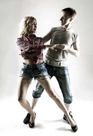 make love: happy young couple dancing, against studio background