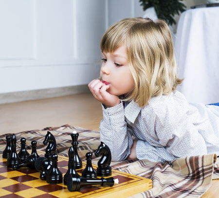 prodigy: cute blond boy playing chess on the floor at home Stock Photo