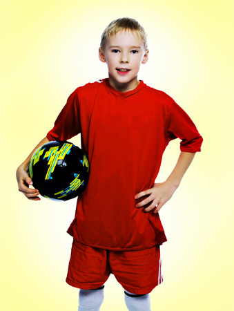 nine year old: nine year old boy dressed as a football player, isolated against yellow studio background