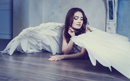 angel alone: beautiful young model with angel wings in the studio
