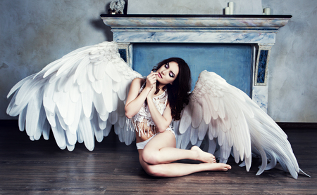 beautiful sad young model with angel wings in the studio