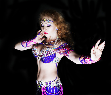 ginger hair: beautiful belly-dancer with long ginger hair and arabic makeup, isolated against black studio background